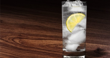 Gin & Tonic mit einer Zitrone auf einem Holztisch